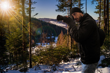 photographer in snowy coniferous forest at sunset