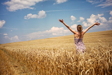 Young woman in summer dress standing in wheat field