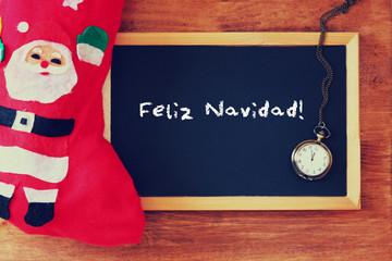 red sock and blackboard with feliz navidad greeting . christmas