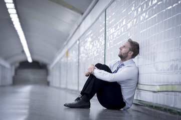 Young businessman in depression sitting on ground street subway
