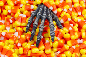 Scary skeleton hand coming out of pile of candy corn