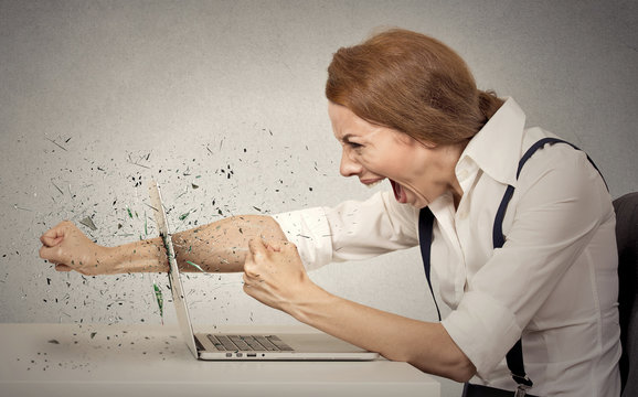 Furious businesswoman throws punch into computer, screaming