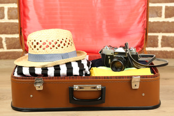 Female clothes in old suitcase on brick wall background