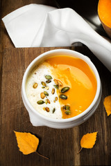 Pumpkin Soup with whipped cream and pumpkin seeds in a white pla