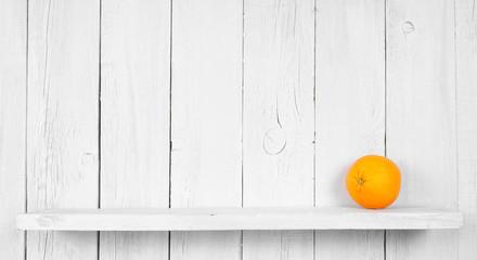 Orange on a wooden shelf.