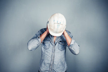 Blue collar worker covering his ears