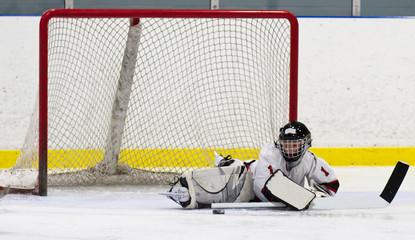Child hockey goalie making a save