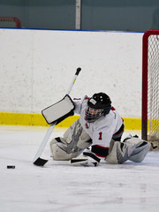 Young ice hockey goaltender making a save