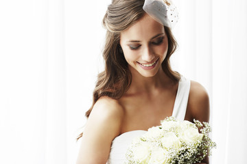 Young bride in wedding dress holding bouquet, studio shot .
