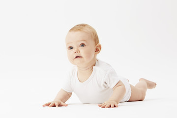Young baby girl crawling on front, studio.