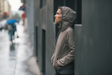 Portrait of fitness woman standing near building in rainy city