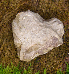 Stone heart and wooden background.