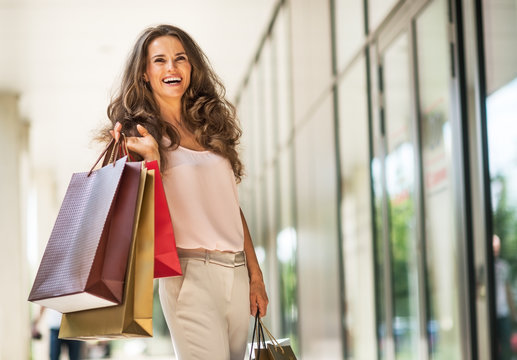 Portrait of happy young woman with shopping bags
