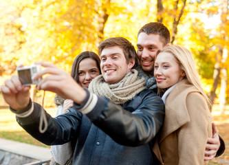 group of smiling men and women making selfie