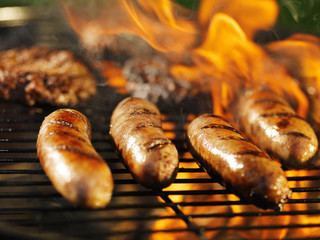 Acrylic Prints Grill / Barbecue bratwursts cooking on flaming grill