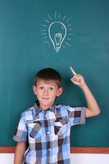 Schoolboy at blackboard in classroom