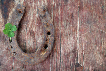 Wall Mural - Old horse shoe,with clover leaf, on wooden background
