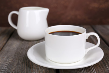 Cup of coffee and cream in milk jug