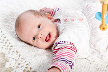 Smiling Baby Girl Lying on Back Looking at Camera