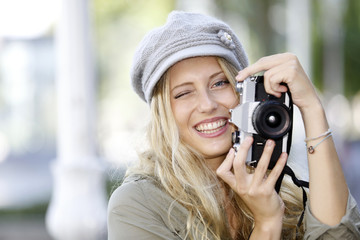 Trendy girl taking pictures with vintage camera