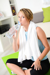 healthy young woman drinking mineral water fitness at home