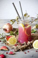 pomegranate and lemon smoothie on glass jar with two straw