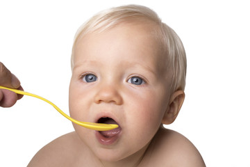 One year old boy eating with spoon