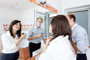 Couple in the bathroom getting ready for work