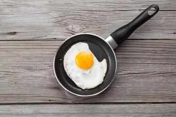In de dag Gebakken Eieren Fried egg in a frying pan, on an old wooden table