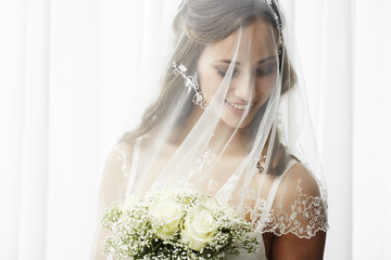 Excited young bride in veil holding bouquet.