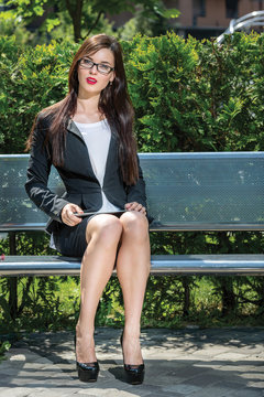 Beautiful businesswoman is sitting on the bench. Working with ta