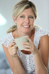Relaxed woman having hot tea at home