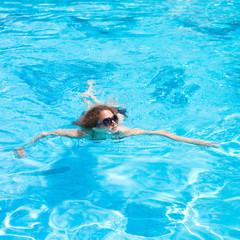Девушка плавает в бпссейне