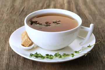 Cup of tasty herbal tea with thyme on wooden table