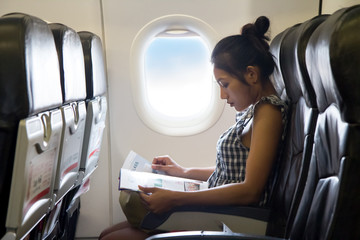 Young woman sits in a chair of the airplane Wall mural