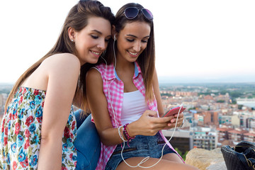 Beautiful girls sitting on the roof and listening to music.