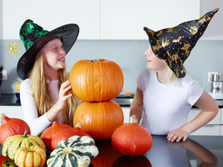 Two girls with pumpkins in the kitchen