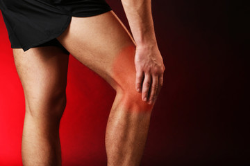 Pain concept.Young man with knee pain