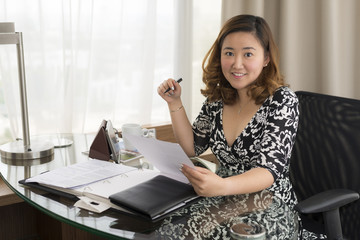 Smiling Asian business woman holding paper and pen
