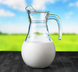Jug of milk on meadow background. Half full pitcher