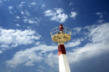 Metal lighthouse under cloudscape sky