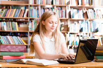 pretty female student typing on notebook in library