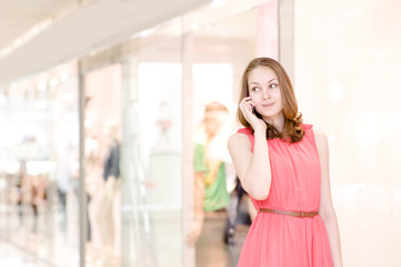 Young woman talking on the phone at the mall