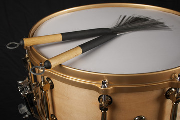 Brushes on a copper snare drum against a black background