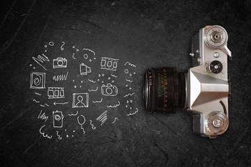 top view of old camera over blackboard and infographics sketches
