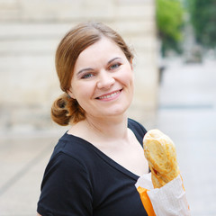 Young woman with fresh baguette on street of a city in France.