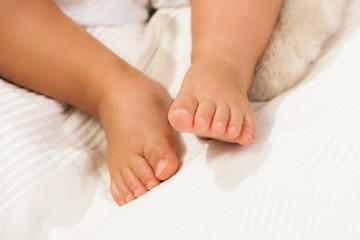 Gambe di un neonato sdraiato su un lenzuolo bianco