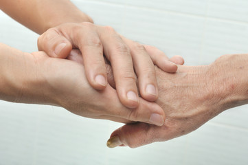 Young male hand holding an old woman's hand