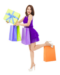 smiling young woman holding shopping bag and a gift box