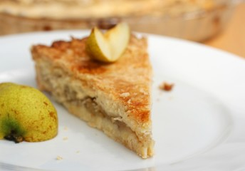 Piece of fresh homemade pear pie with fresh pear slice